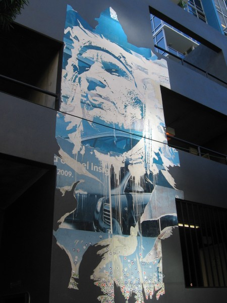 Mural of Native American appears tattered on a modern building.