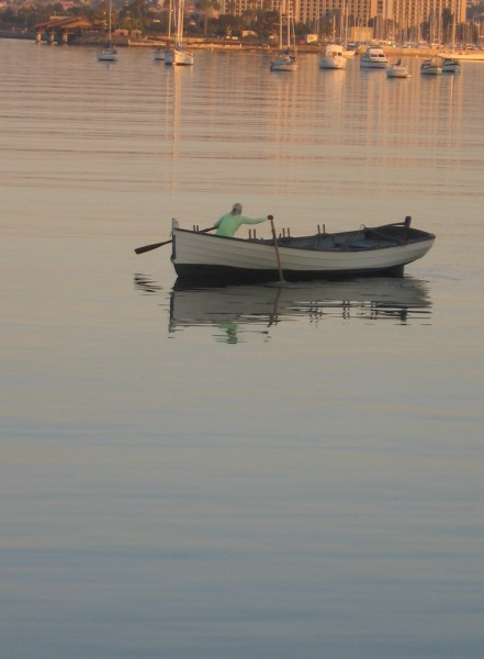Lone rower on San Diego Bay in golden morning light.