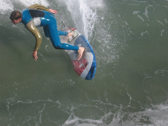 Surfer rides a wave just below the Imperial Beach pier.