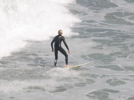 Guy on surfboard just coasting along the foamy ocean surface.