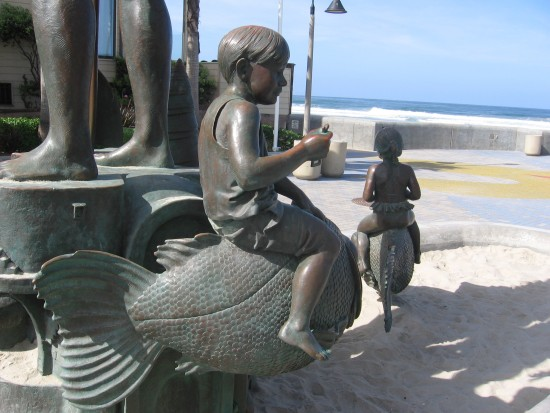 Child rides a fish near the beach.