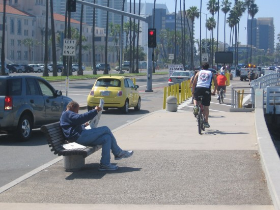 Biking and reading a newspaper along Harbor Drive.