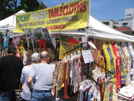 Tuscany Italian tablecloths line a vendor's tent.