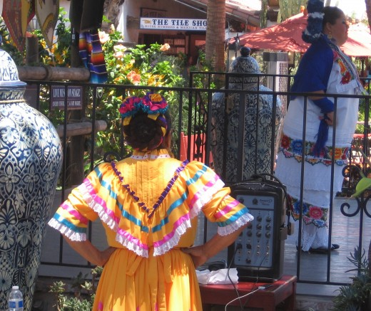 One Mexican folk dancer watches another on stage.