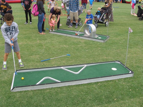 Kids play miniature golf on the grassy lawn.