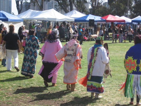 Mothers in native costume in a large round dance.