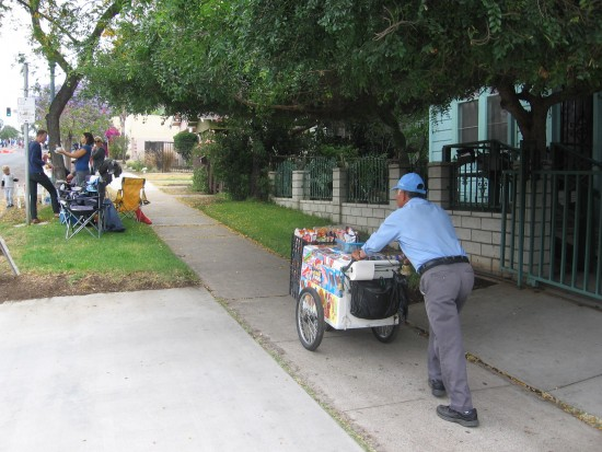Man pushes Ice cream cart up 25th Street hill.