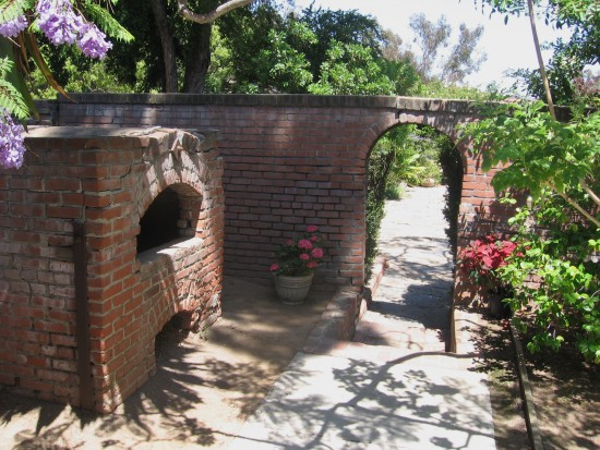 Outdoor archway and oven are part of the delightful scenery.