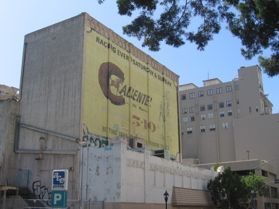 Large old Caliente racetrack sign on building.