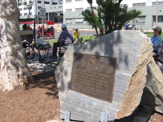 Pedicab drivers wait near Pearl Harbor plaque.