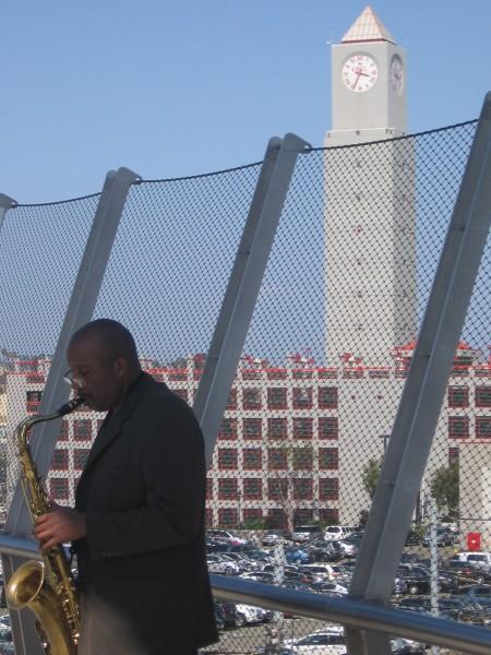 Clock tower above musician on Harbor Drive bridge.