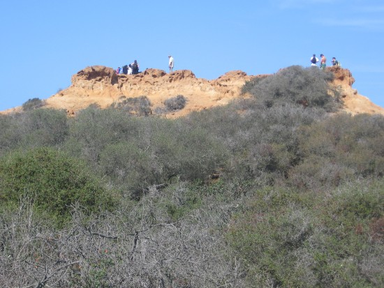 People enjoy vistas from atop sandstone formation.