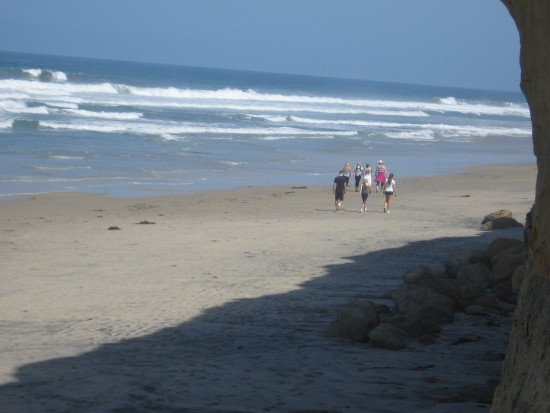 People walk north along Torrey Pines State Beach.