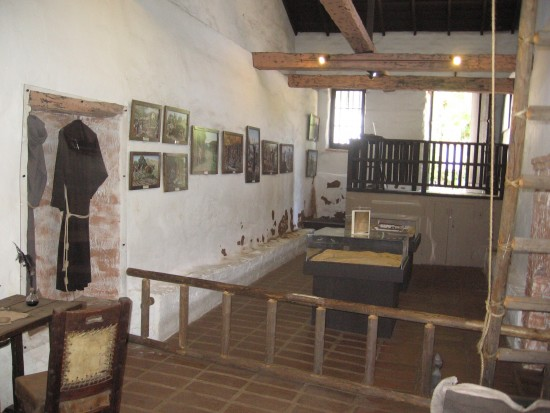 Padres' living quarters with adobe walls and wooden beams.