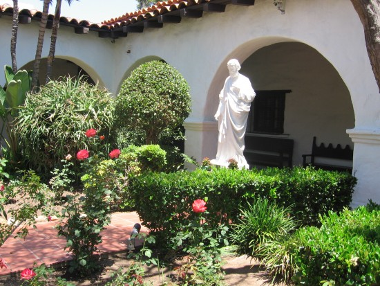 Garden courtyard by sanctuary contains sunlit statues.