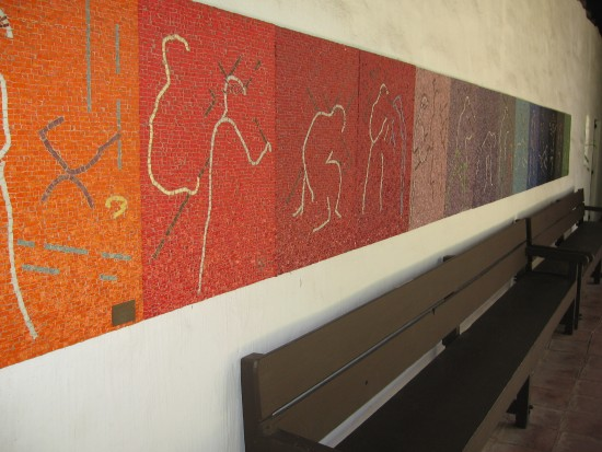 Modern abstract mural lines wall above wood bench.