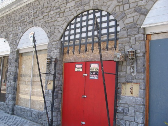 Old door with spears and portcullis is locked shut.