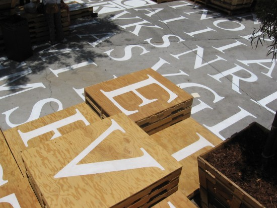 Letters on the ground and pallets form a big word find puzzle.