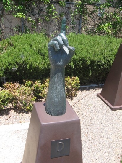 Bronze hand signs the letter D.