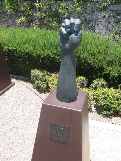 Bronze hand signs the letter M.