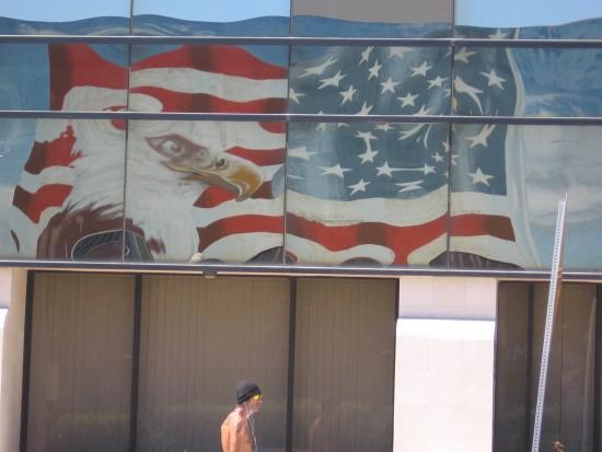 Reflection on windows of big American flag mural.