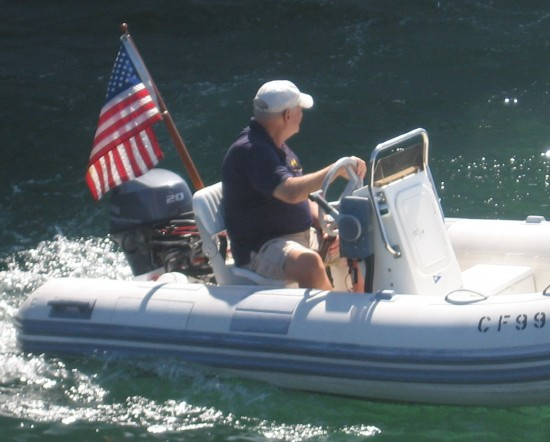 Small boat cruises San Diego Bay with flag.