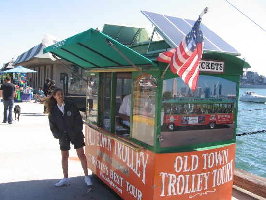Old Town Trolley Tours booth has a flag out.
