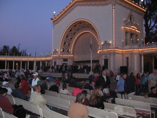 Night descends and people stretch their legs during intermission.
