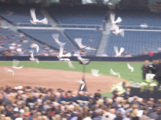 White doves are released near the stage as program begins.