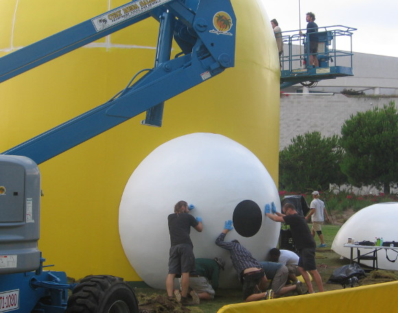 Workers push huge Homer Simpson eyeball into a big yellow head.