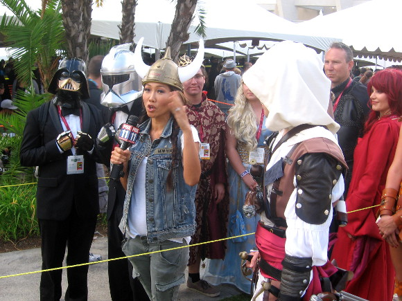 News reporter talks with very elegantly dressed Star Wars characters.