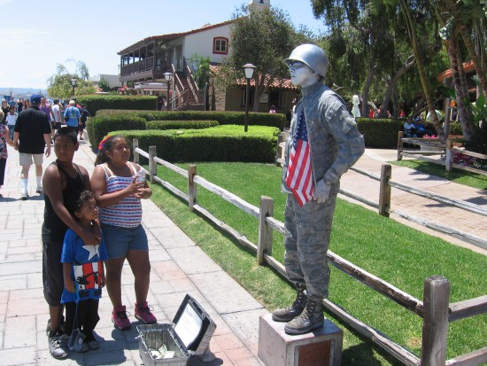 Street performer poses with red, white and blue.