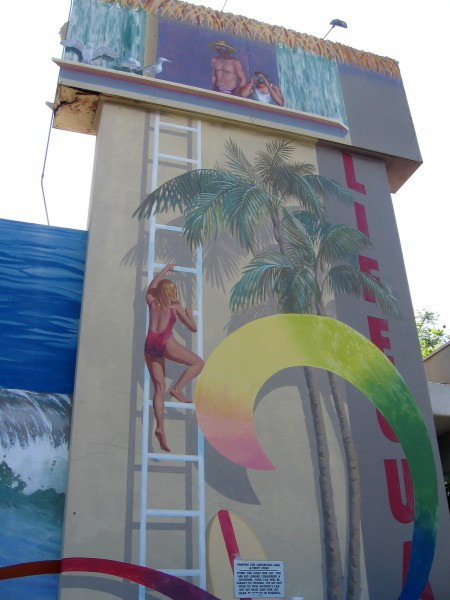 Mural shows lifeguard climbing a tower among palms.