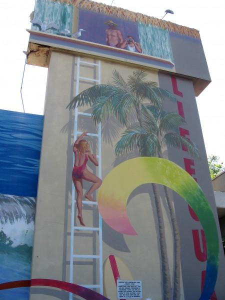 Mural shows lifeguard climbing a tower among palms.