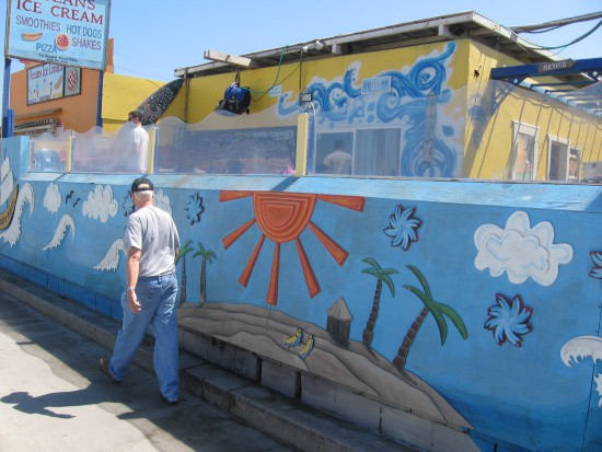Youth hostel by Pacific Beach boardwalk has sunny mural.