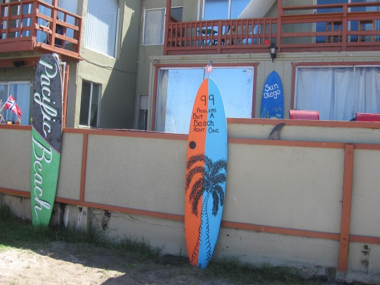Colorful surfboards by beach contain happy messages.