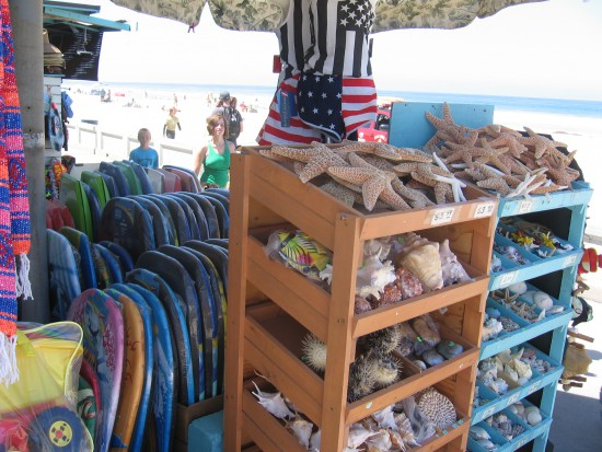 Shells and boogie boards line the boardwalk for passing tourists.