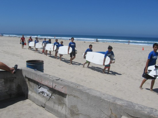 Kids learning to surf file along carrying surfboards.