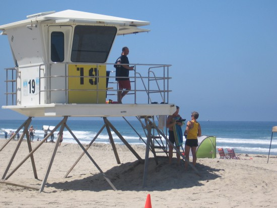 People chat as a lifeguard watches the beach from a tower.