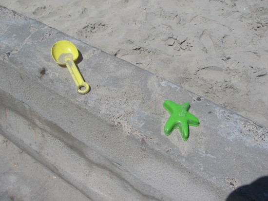 Colorful beach toys left on the concrete sea wall.