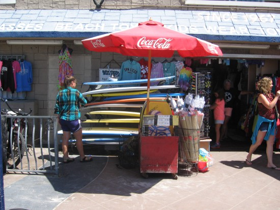 Lady looks through a high stack of surfboards.
