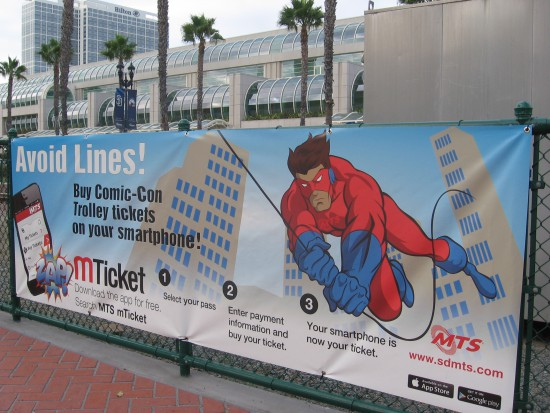 Gaslamp trolley station has superhero sign about a ticket app.