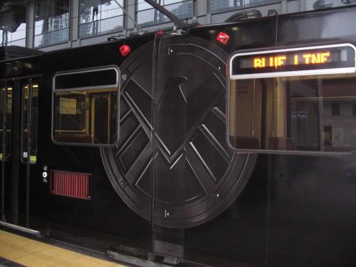 Close-up image of the S.H.I.E.L.D. emblem on a black trolley.