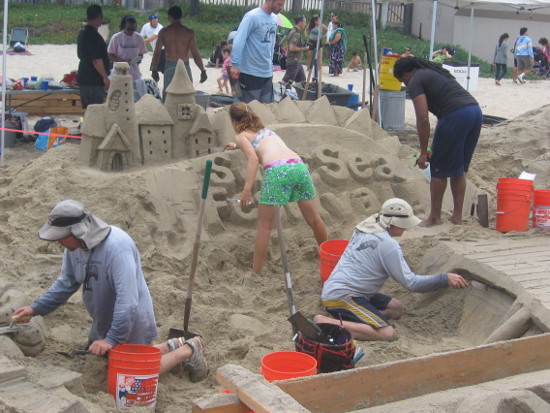 Huge, complex sand sculpture with many team members working.