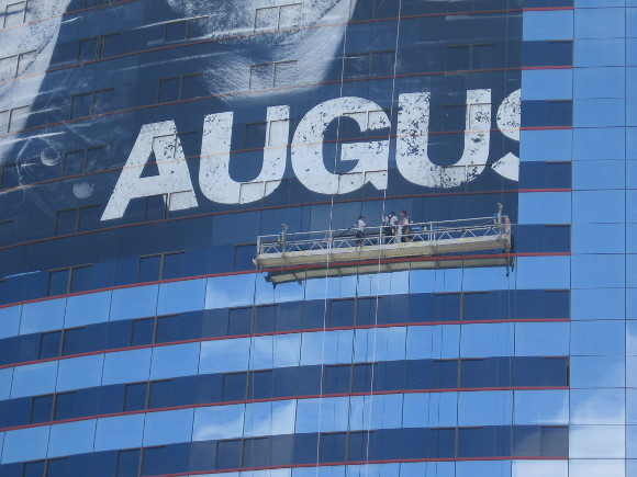 Workers on platform apply Legends graphic on building for Comic-Con!