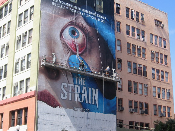 Worker paints worm dangling from a huge bulging eyeball!