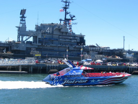Patriot speed boat leaves dock, passing USS Midway.