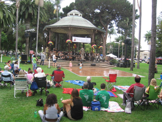 People enjoy music at the bandstand on a warm summer day.