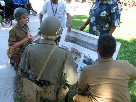 Nearby, guys in vintage military uniforms look at some historical images.