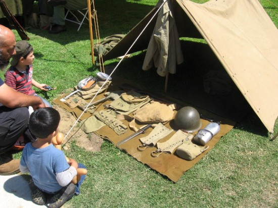 Kids check out a tent and various items carried by soldiers decades ago.